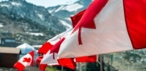 Canada flags waving at the wind in mountain scenario