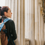A young girl traveler or tourist or student with a backpack travels