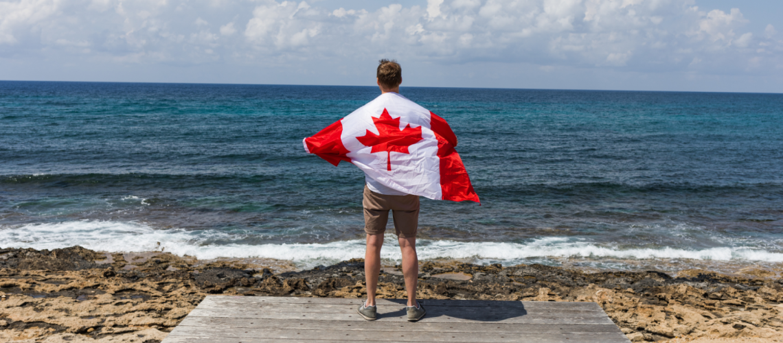 Man Holding Canada's Flag at the Beach