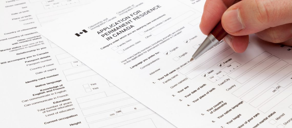 Close-up on the hand of a man filling an application form to obtain a Permanent residence in Canada.